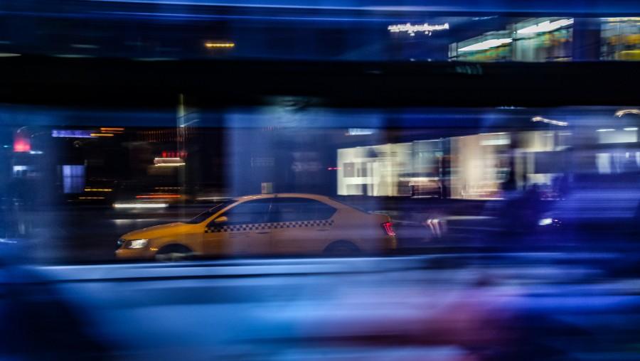 Photo of taxi, taken through bus