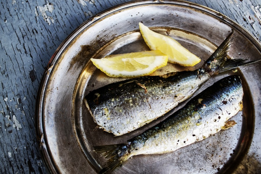 Sardines and Lemon on a Metal Plate with Broken Paint Wooden Background