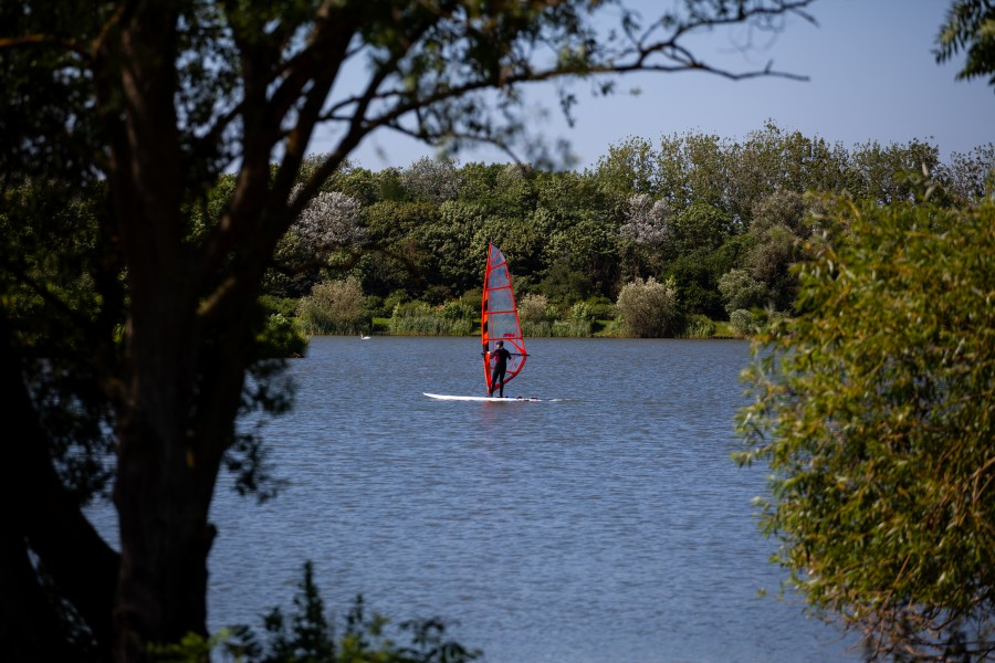 Man wind surfing on lake