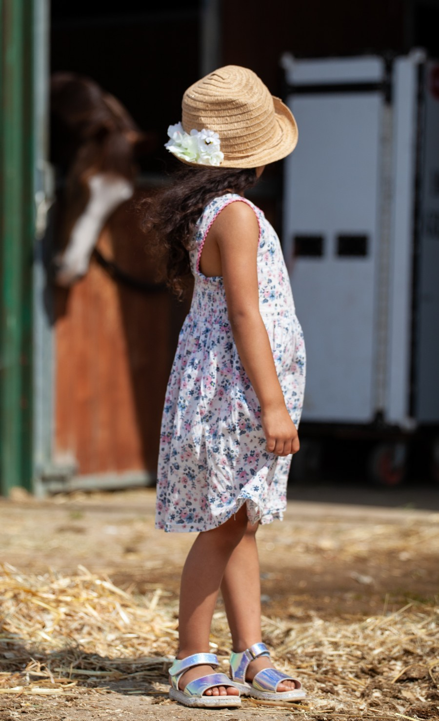 child in hat looking at horse