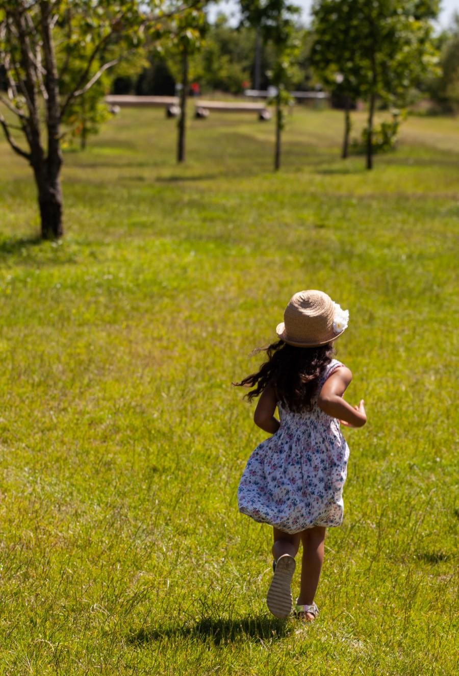 Child in hat runs on grass