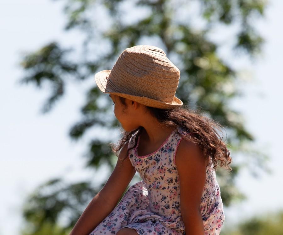 child in hat looking over left shoulder