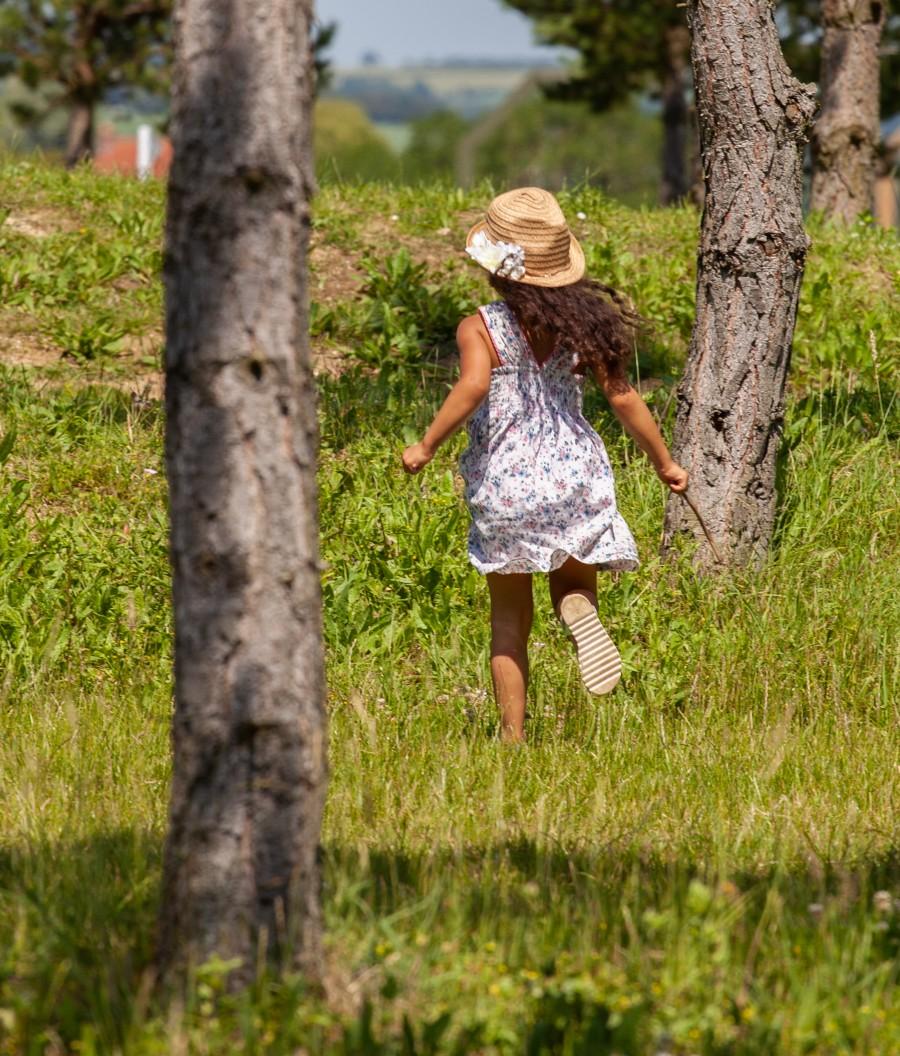 Child in hat running between trees