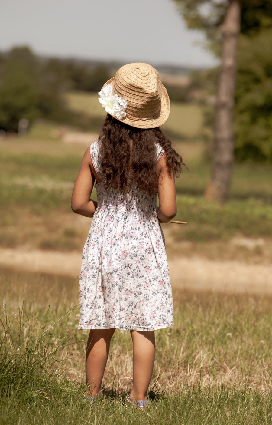 Child in hat looking over the fields
